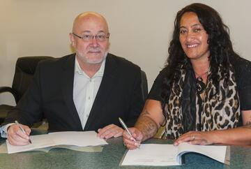 Rangiwewehi Charitable Trust development team leader Gina Mohi and GNS Science chief executive Michael McWilliams sign the agreement that covers working together for mutual benefit. Photo: Margaret Low, GNS Science