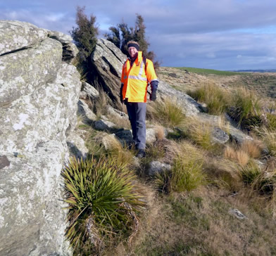 Geologist Adam Martin, of GNS Science, examines a rock outcrop to compile information for the new geological map of East Otago. Photo - GNS Science