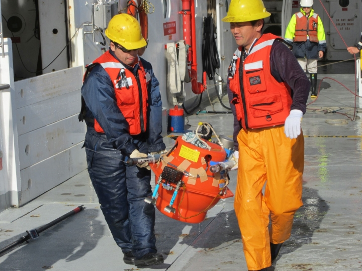 : Seafloor deployment: Japanese scientists prepare a seafloor instrument prior to deployment off the east coast of the North Island. These instruments sit on the seafloor and record  earthquake activity inside the Hikurangi subduction zone.   Photo - Steven Plescia, University of Colorado