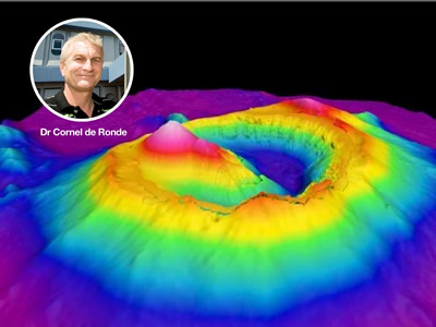 Voyage co-leader Cornel de Ronde superimposed on a 3D image of Brothers submarine volcano showing the cone where scientists will drill to explore the internal plumbing of the volcano. Image – Darren D'Cruz, GNS Science