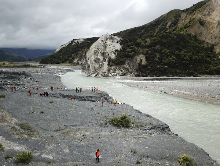 Field trip participants spread along the uplifted scarp of the Papatea fault as it crosses the Clarence River. At this location, the river bank on the left side of the photo was uplifted about 9 m relative to the other side of the river.  Rapid incision by streams and the river through this newly uplifted riverbank is creating rapids and impressive erosional features.