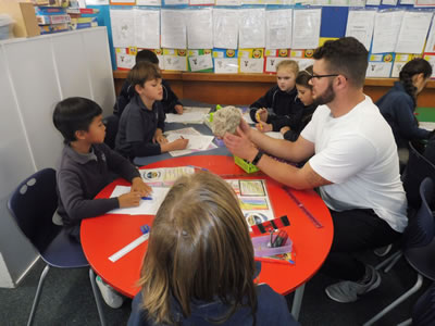 Ben Payne of GNS Science shows students at Hilltop School in Taupo a lump of pumice during an interactive session on the supervolcanoes of the Central North Island. Photo – Helen Gibson, Hilltop School