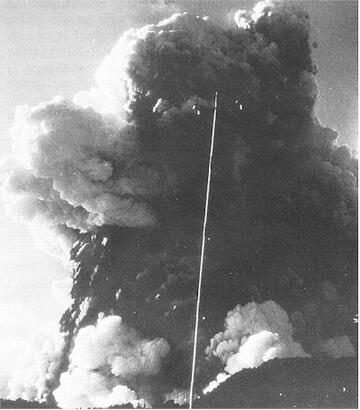 b) Climax of the eruption at the main crater, photographed a few seconds after (a) above. A dense eruption cloud has reached an estimated height of 1.2 km. Rocks falling in spearhead thrusts, on ballistic trajectories, can be seen on the left of the column, just under the high mass of light-coloured steam. White steam rising at the base of the column marks the passage of base surges.