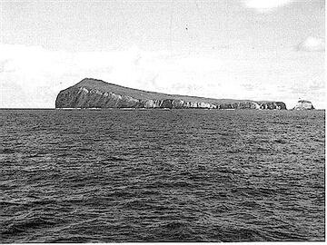 Figure 9. (a-b) Macauley Island. photographs by B.J. Scott. (a)View looking north-west showing light-coloured Sandy Bay Ignimbrite overlying dark lava flows produced by earlier eruptions. Haszard Islet can be seen on the right.