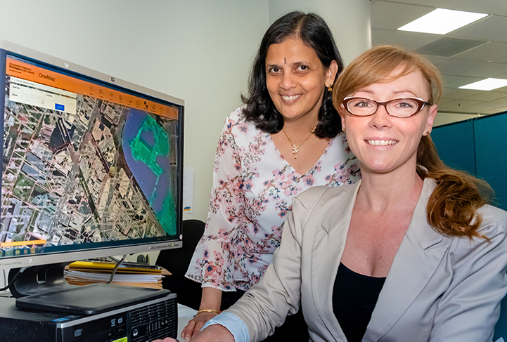 Dr SR Uma and Hayley Moselen with an aerial image of Wellington's CBD