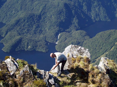 Geologists went to extensive lengths to do accurate field mapping during the compilation of the new map series. Here Richard Jongens of GNS Science samples rocks in Fiordland.