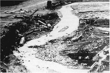 Figure 1: An aerial view northwards of the scene at Tangiwai after the 24 December 1953 lahar. The railway line between Ohakune and Waiouru runs across the photo from left to right. The engine of the train lies on the bank to the left, with railway carriages scattered on both banks downstream. The damaged road bridge is in right foreground. (NZ Herald)