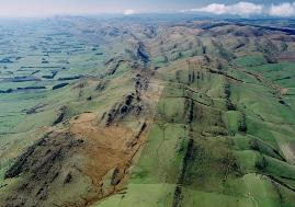 Looking east along the Hokunui Hills. The lines of rock beds form the northern limb of the Southland Syncline, with older layers on the left (North) and younger to the right (South). In the foreground these beds are actually overturned slightly. Image: GNS Science.