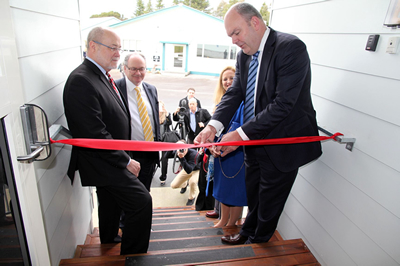 Science and Innovation Minister Steven Joyce, accompanied by the Chief Executive and Chair of GNS Science, cuts a ribbon to formally open  the revamped laboratories.