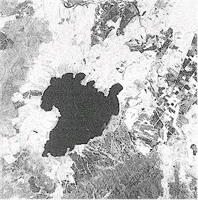 Satellite photograph of Lake Taupo and the surrounding area. Taupo volcano, comprising several calderas (collapsed volcanoes) makes up the northern part of the lake. The surrounding lighter-coloured region is the area most thickly covered by the deposits of Taupo eruption 1800 years ago. Landstat thematic mapper ™ image taken in 1991 courtesy of Landcare Research New Zealand Ltd.