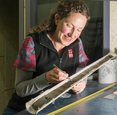 Research co-author Dr Ursula Cochran examines one of the sediment cores from Big Lagoon. Photo Margaret Low, GNS Science